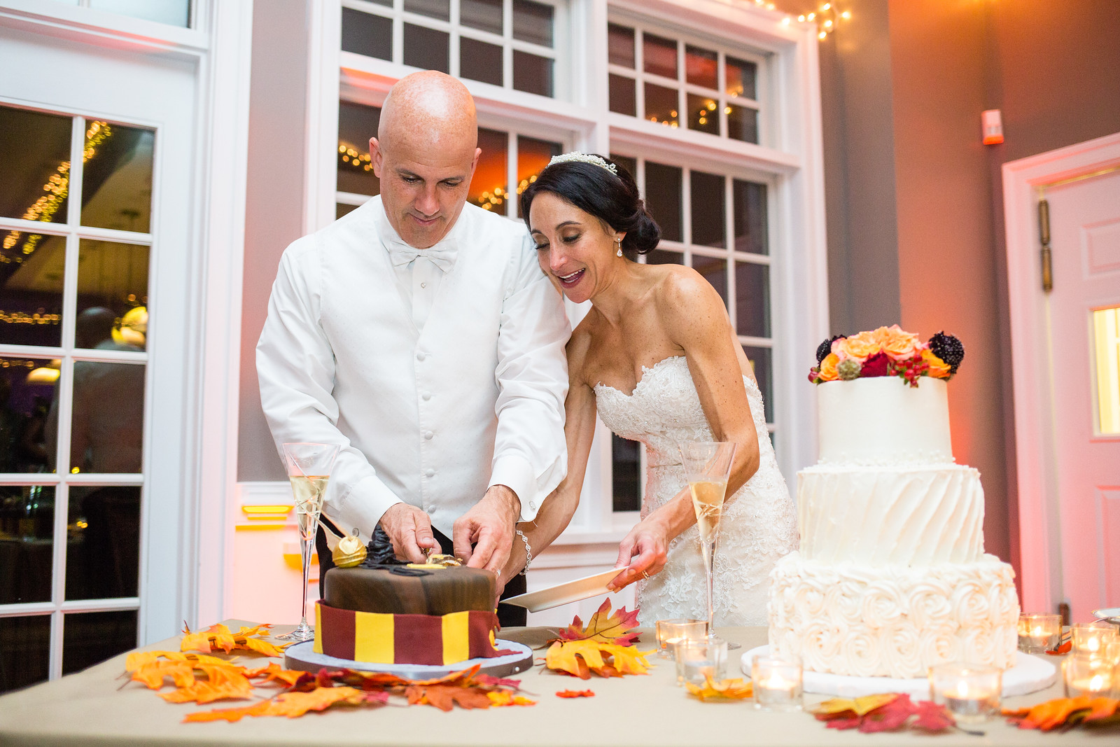 bride and groom cutting wedding cake by perfect planning events